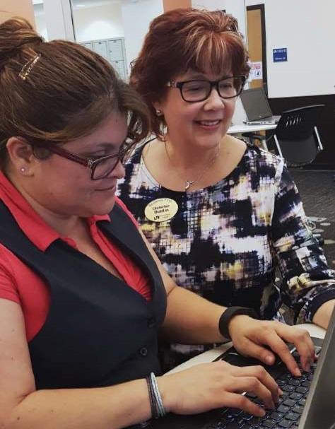 MDC's Medical Coder-Biller Program Coordinator Christine Dundas, right, works with a student at Medical Campus.