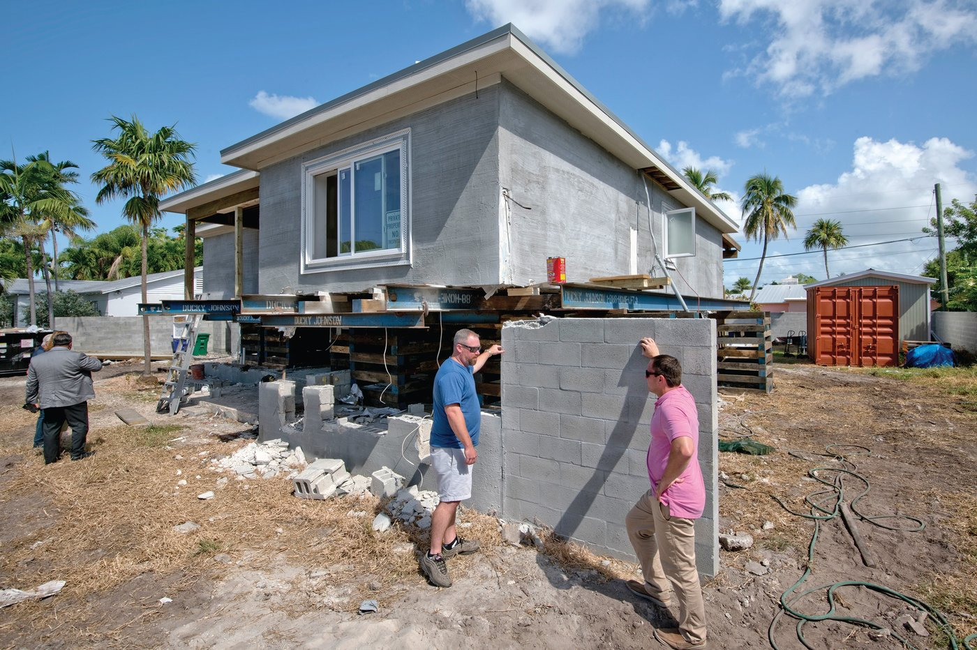 RISE TIME. Danny McKearan, right, of Ducky Johnson Home Elevation Services, speaks with homeowner Peter Batty Jr. about the steps involved in raising his block-style home in Key West. Batty's home is the first non-wood construction home to be successfully elevated in the entire Florida Keys.