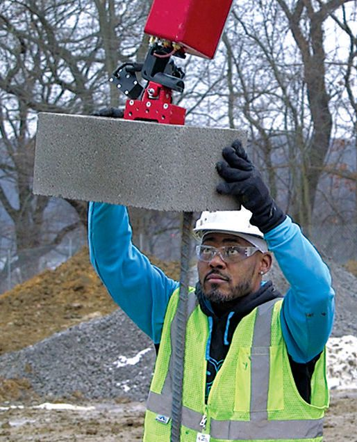 A mason easily maneuvers an oversized block over rebar on an elementary school project in Pennsylvania