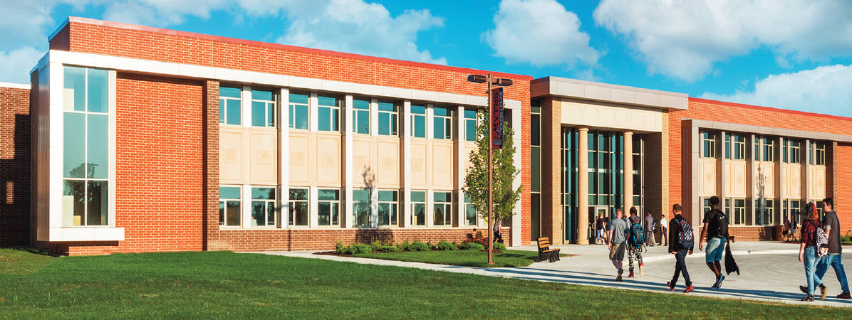 Custom cast stone columns and panels with educational motifs add personality to the entry. Citadel, Saddle and Varsity colored Boral Brick (now Meridian) adorn the rest of the exterior of the 300,000 sf high school.