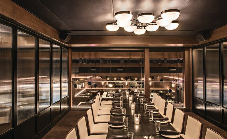The main dining room at RPM Steak features dark wood tables, tan leather booths and dramatic white curtains.