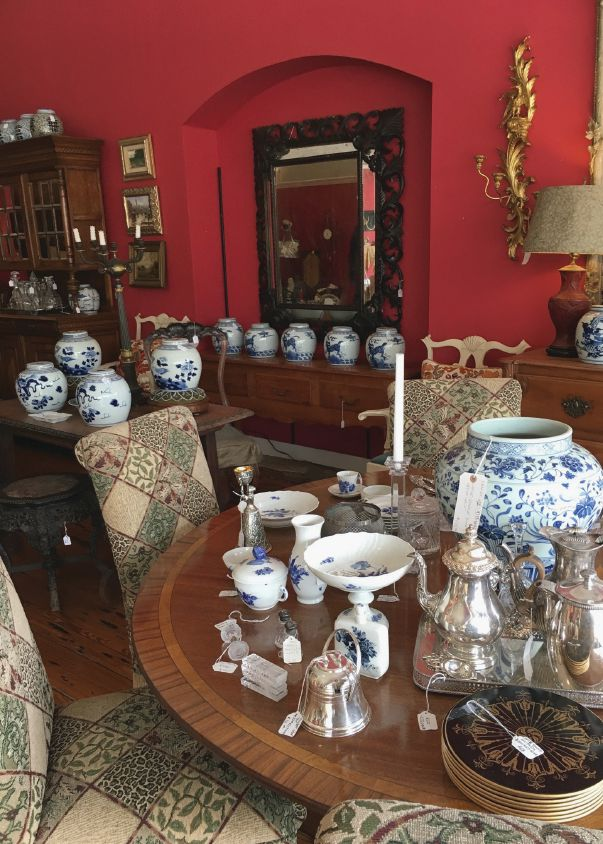 The reproduction English Regency mahogany satinwood and rosewood dining table is set with pieces of silver, crystal and blue and white Royal Copenhagen dishes from Denmark.  Upholstered chairs, chests, lamps, sconces, framed paintings, ginger jars, an enormous mirror and a secretary from England fill just one corner of the store.