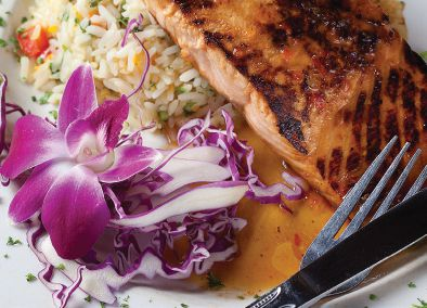 A signature small orchid graces many of the plates, including the grilled Thai chile-glazed salmon ilet. 2 of 7