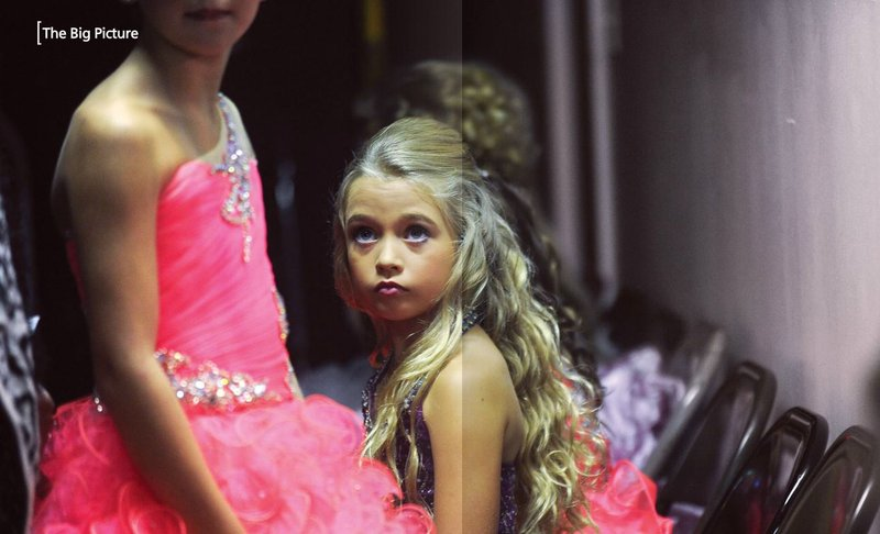 Little Fair Princess pageant contestant Blakely Bagett looks nervously at another contestant as they get ready to go onstage at the Cullman County Fair in Alabama.  Lions have run the fair since 1954.  See the story on page 22.