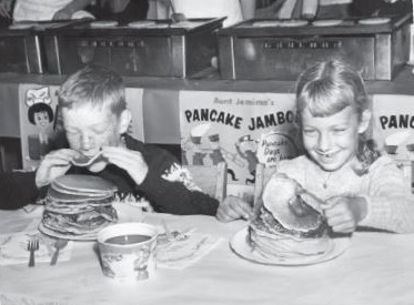 Children pile high the pancakes at a Lions' breakfast in East Weymouth, Massachusetts, n 1964.
