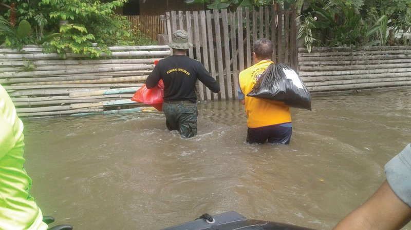 Members of the Milagro Melvin Jones Lions Club in Ecuador carry supplies to flood victims.  Lions are sure to complete the centennial goal of serving 100 million people.