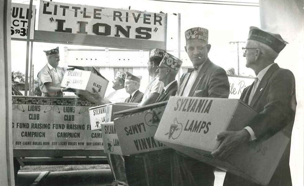 Little River Lions in Florida take part in their annual light bulb sale in 1961 to pay for eye exams and glasses for those in need.