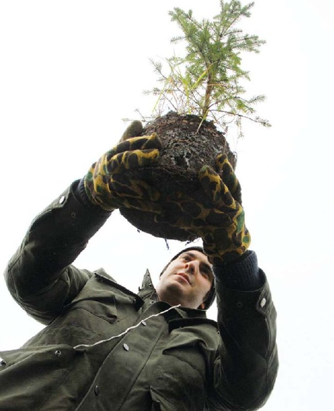 Andrew Shenkman prepares to plant a tree in Holland Marsh in Ontario, Canada, a conservation initiative supported by the Bradford Lions Club.  Lions worldwide are expected to easily meet the Centennial goal of benefiting 100 million people by June 2018.