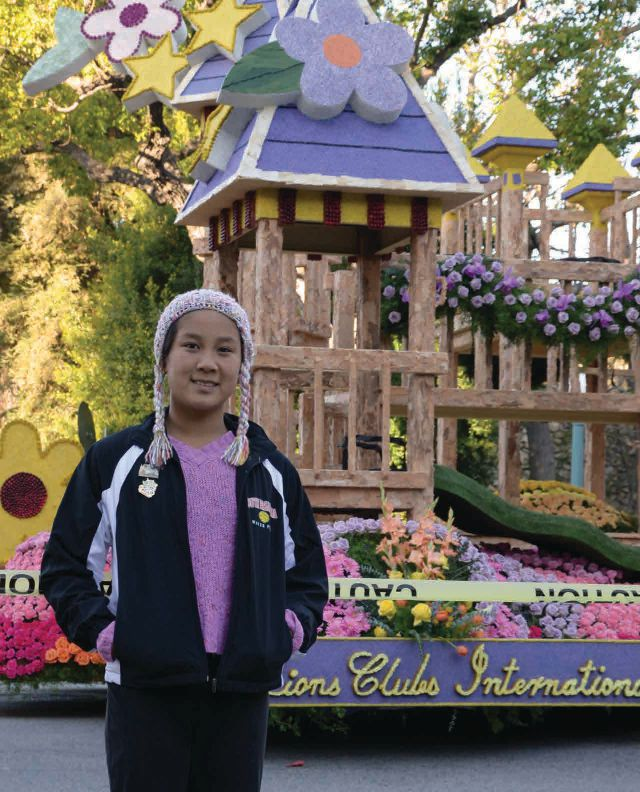 Glenda Chen stands proudly in front of the Lions' float at the Rose Parade in California.