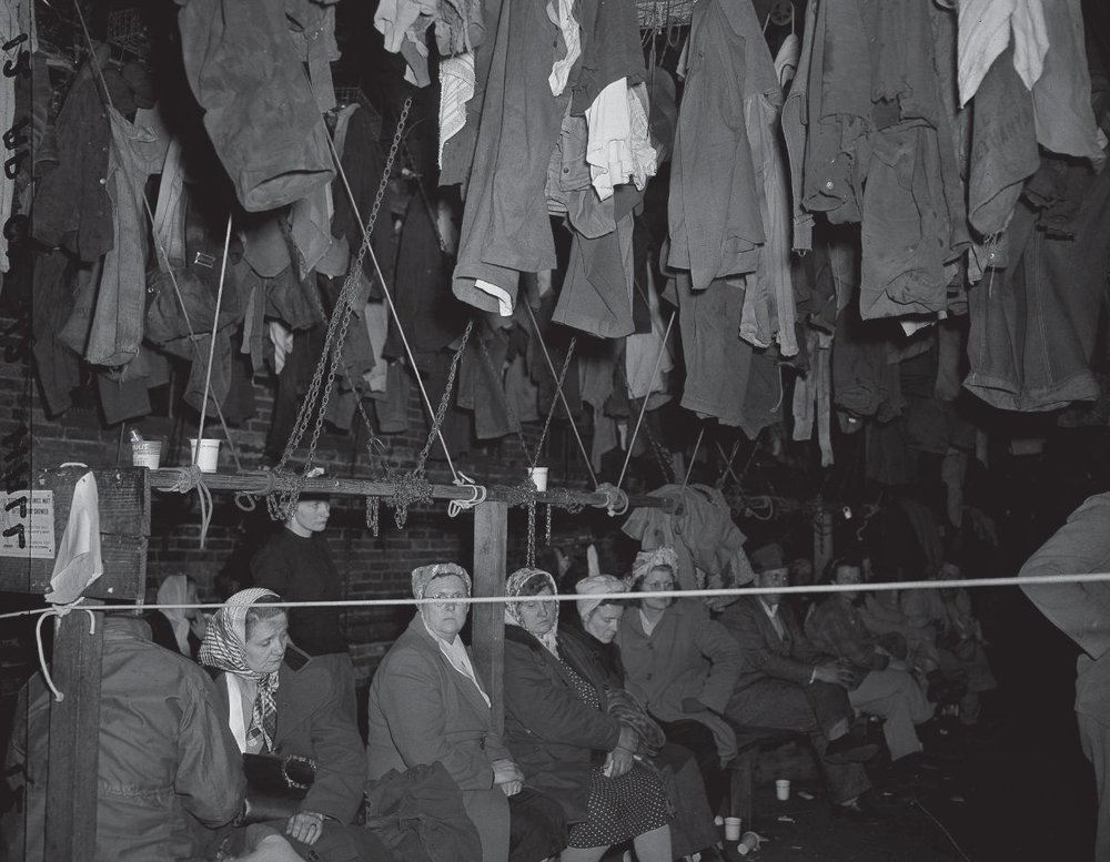 Wives and mothers of miners trapped by the explosion in the Centralia mine wait in the company washhouse.  Hanging above them is miners' clothing.