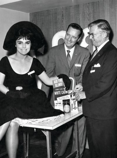 Actress Erin O'Brien, the queen of the North Hollywood Lions White Cane Drive in California in 1959, buys the first cane from Lions Carl Auer (center) and Jack McGuire.