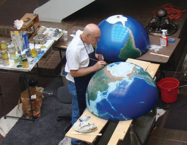 Don Ecklund paints the globe at headquarters