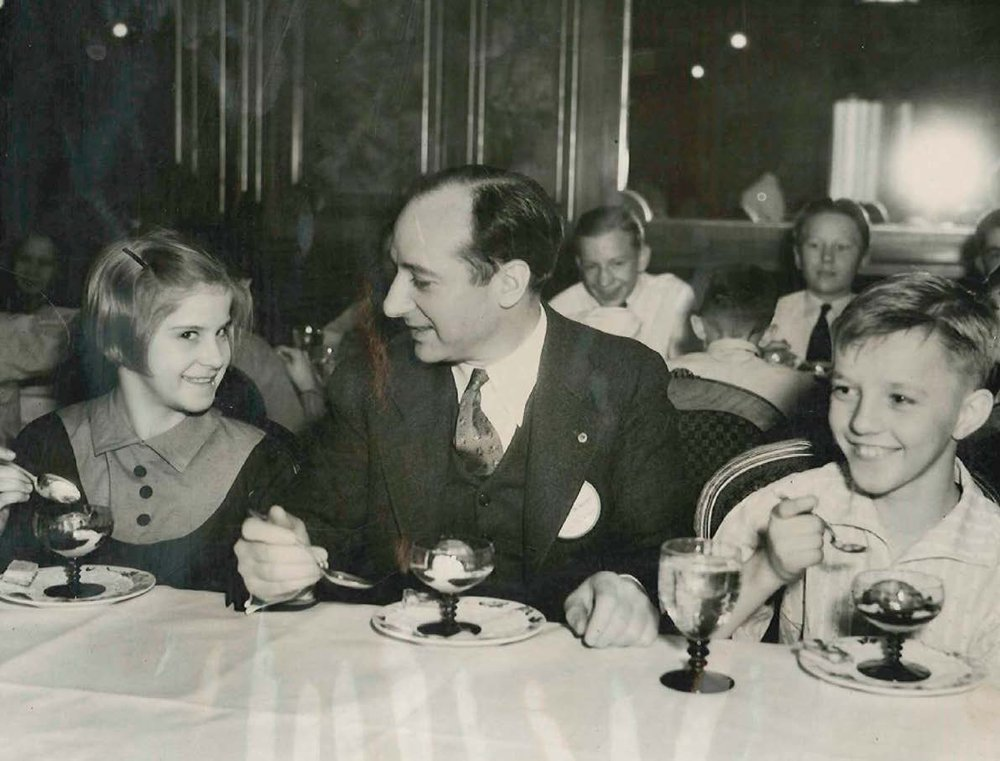 Dr. A. P. Wilkinson of the Detroit North End Lions Club in Michigan shares a treat at a Lions' dinner for orphans in 1933.