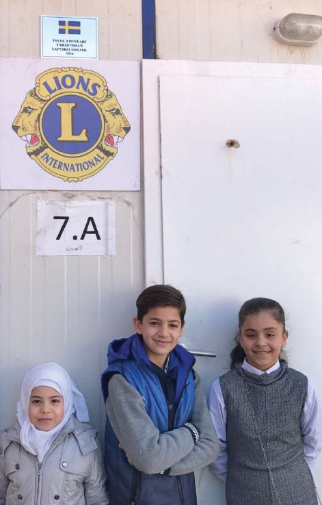 Abdulrezak (center), his sister, Esma (right), and another child, also a Syrian refugee, stand outside the container classroom in Turkey made possible by Swedish Lions.