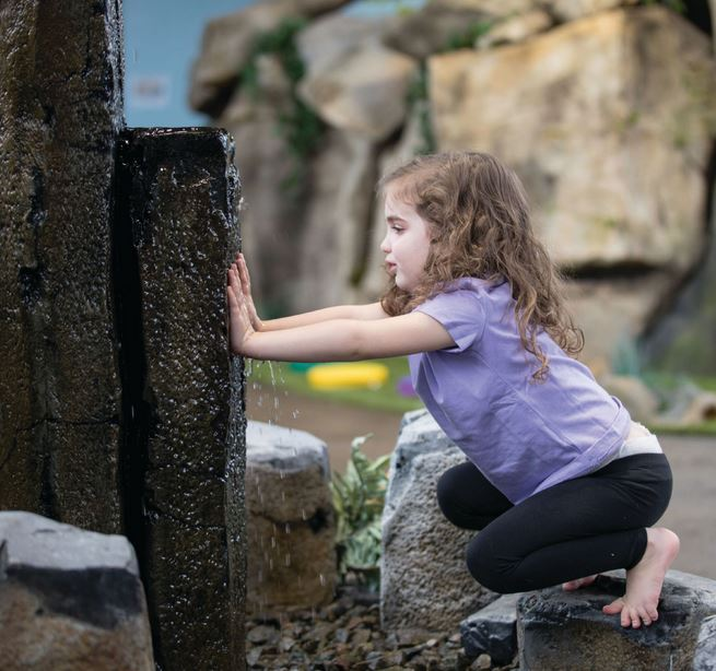 Madilyn Mau, a 3-year-old with developmental delays, feels water running down a stone at the courtyard.