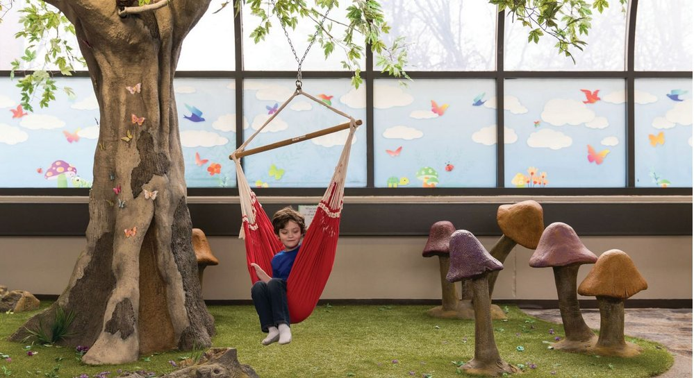 Alex Mau, a 5-year-old with autism, lounges in a swing at the Sensory Courtyard in Fremont, Nebraska.