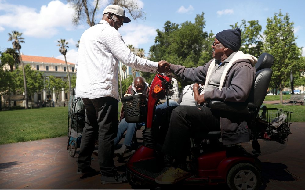 Lion Kevin Martin shakes hands with homeless veteran Sidney Lee Johnson after detailing ways he could help Johnson in San Jose, California.
