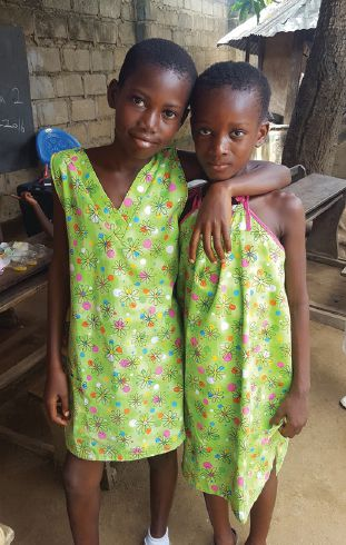 Two orphans in Ghana wear dresses made from old pillowcases.