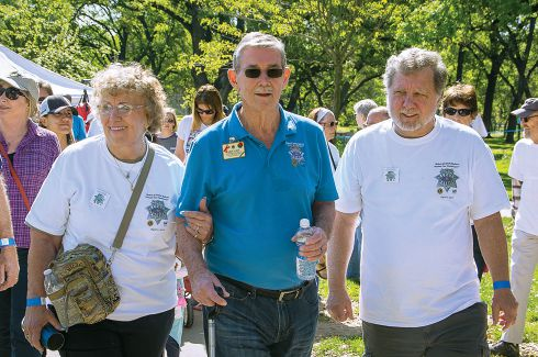 Past International Director Robert G. Smith walks with longtime friends Sylvia and David Darnell. Photo by Tony Santos