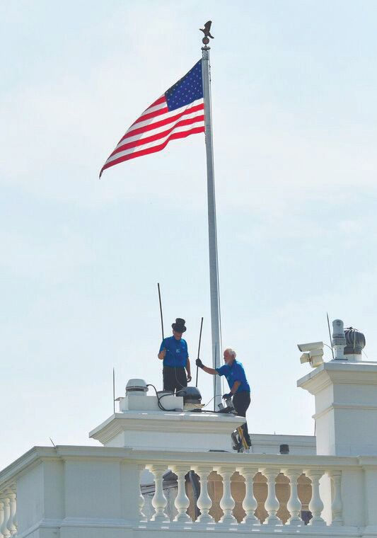Lion Jeff Schmittinger (left) and a helper sweep the White House chimneys for free.