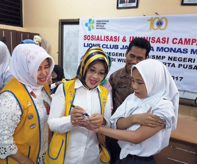 Knowing another child will be protected from measles and rubella, Lions in Indonesia smile at a vaccination event.