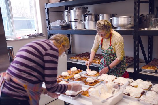 Lions Jennifer McCrary (left) and Jane Ringler make the club's cinnamon rolls, a popular fundraiser.