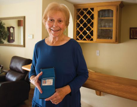 Rogers displays her late husband's wallet. She is at the home of Lion Barry Bialkoski.