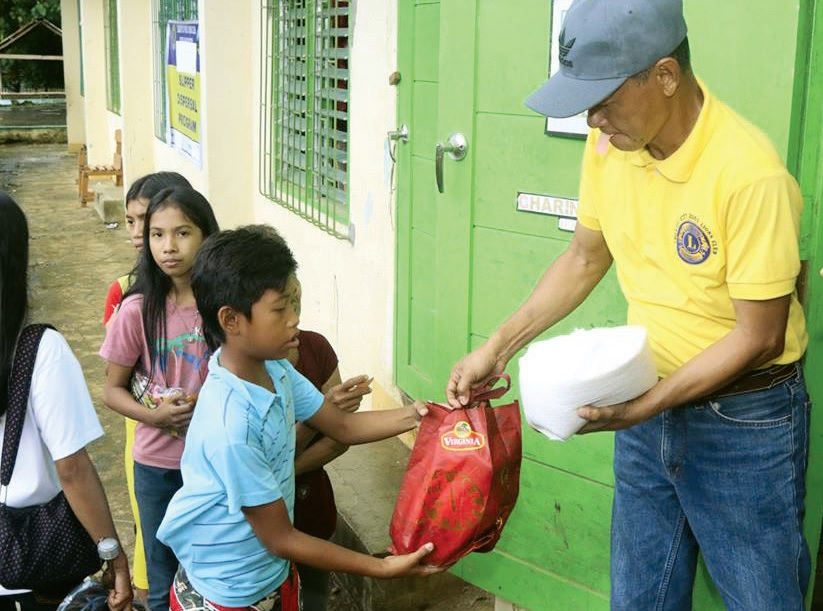 """A Legazpi City """"Host"""" Lion gives food to a needy child in Mancao."""