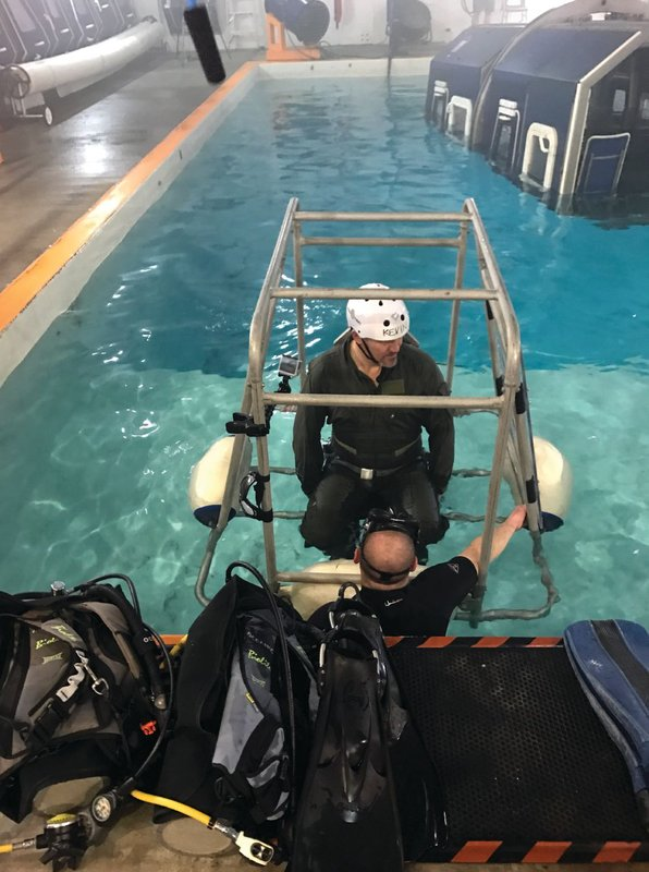Student preparing for Shallow Water Egress Trainer (SWET) to be inverted. Photo credit: Survival Systems USA, Inc.
