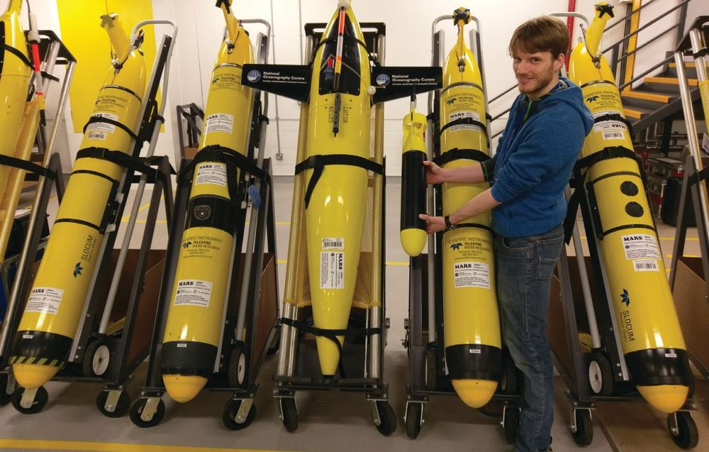 Dr Alex Phillips, lead designer, with ecoSUB-ì against some of the NOC Glider fleet. Photo credit: Planet Ocean Ltd and National Oceanography Centre.