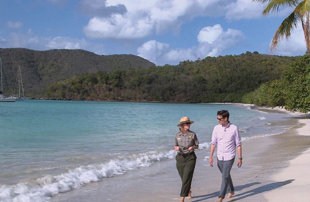 Conor Knighton walks with a park ranger in Virgin Islands National Park. The park covers more than one half of Saint John Island and Hassel Island in Saint Thomas harbor and includes quiet coves, blue green waters, and white sandy beaches fringed by lush green hills. Photo credit: CBS News.