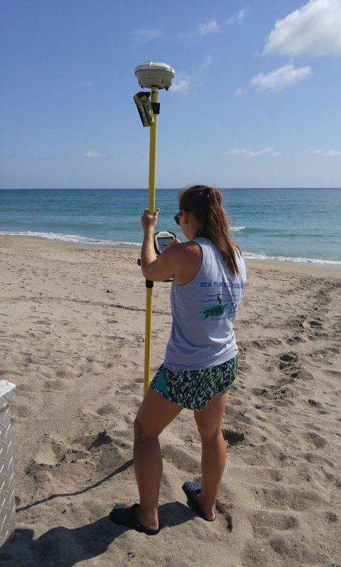 "EAI technician Gabbie Kaminski uses a highly accurate GPS system to record a loggerhead nest location. This instrumentation was used in Martin County for a study evaluating factors such as elevation and slope in a ""turtle-friendly"" beach nourishment template. Photo credit: Niki Desjardin."
