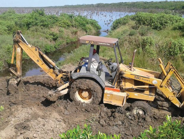 A backhoe at work during the expansion of channels to address hydrological flux at Tuxpan.