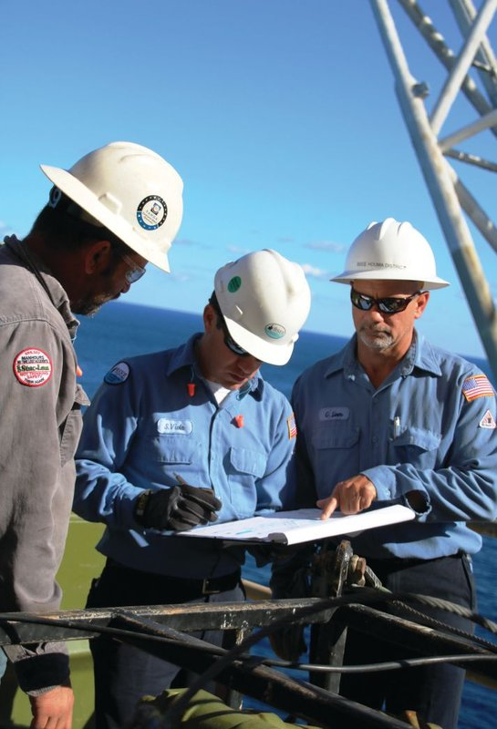 BSEE Inspectors Sammy Viola (center) and Greg Liner review paperwork submitted by Stric-Lan contractor Brian Landry during an inspection on Front Runner October 25.