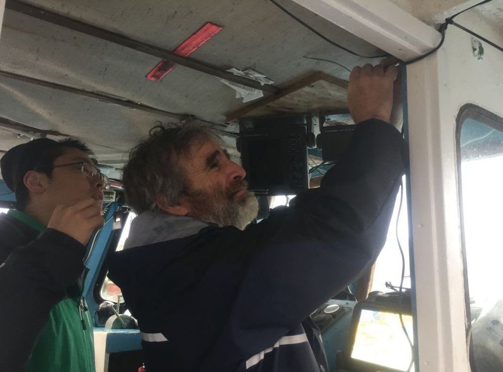 Jim Manning and Xavier of Manning's laboratory outfitting a fishing vessel with temperature probe and telemetric capabilities.