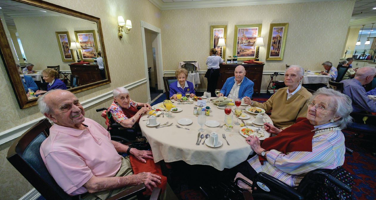 GOLDEN YEARS. The Platinum Club Luncheon is held once a month in the Jefferson's dining room to appreciate the community's centenarian residents. Pictured in blue at top left is 103-year-old Vera Punke. On the opposite page, two women read newspapers in the Jefferson's library.
