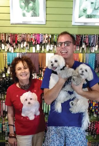 Pam (wearing Maltese shirt) with Tony, holding Vito and Sonny, at Muttropolis, a chic pet boutique for dogs and cats. ALLEN LECHTMAN