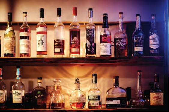 bottles of local spirits line the shelves behind the bar