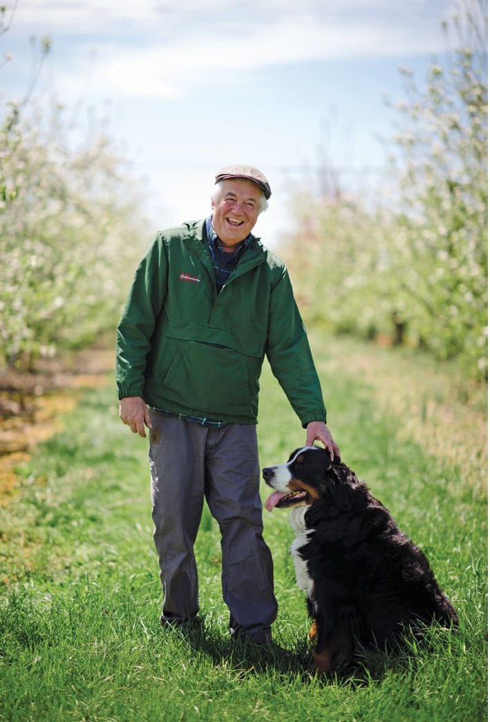 Distillery Lane co-owner Rob Miller and his dog, Kingston, stand among the property's some 4,000 apple trees.