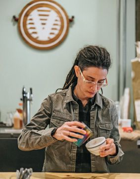 Coffee owner Sarah Walker practices latte art