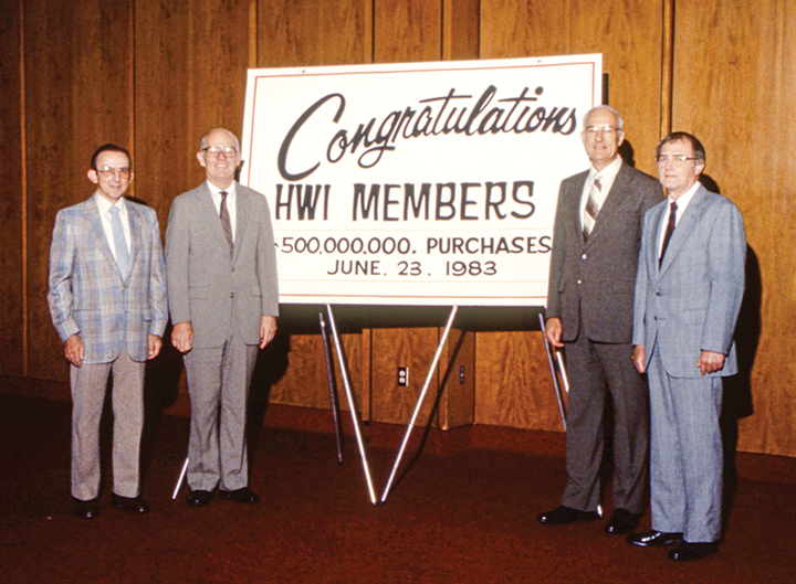 Don Wolf (second from right) congratulates HWI members on reaching $500 million in member purchases in 1983.