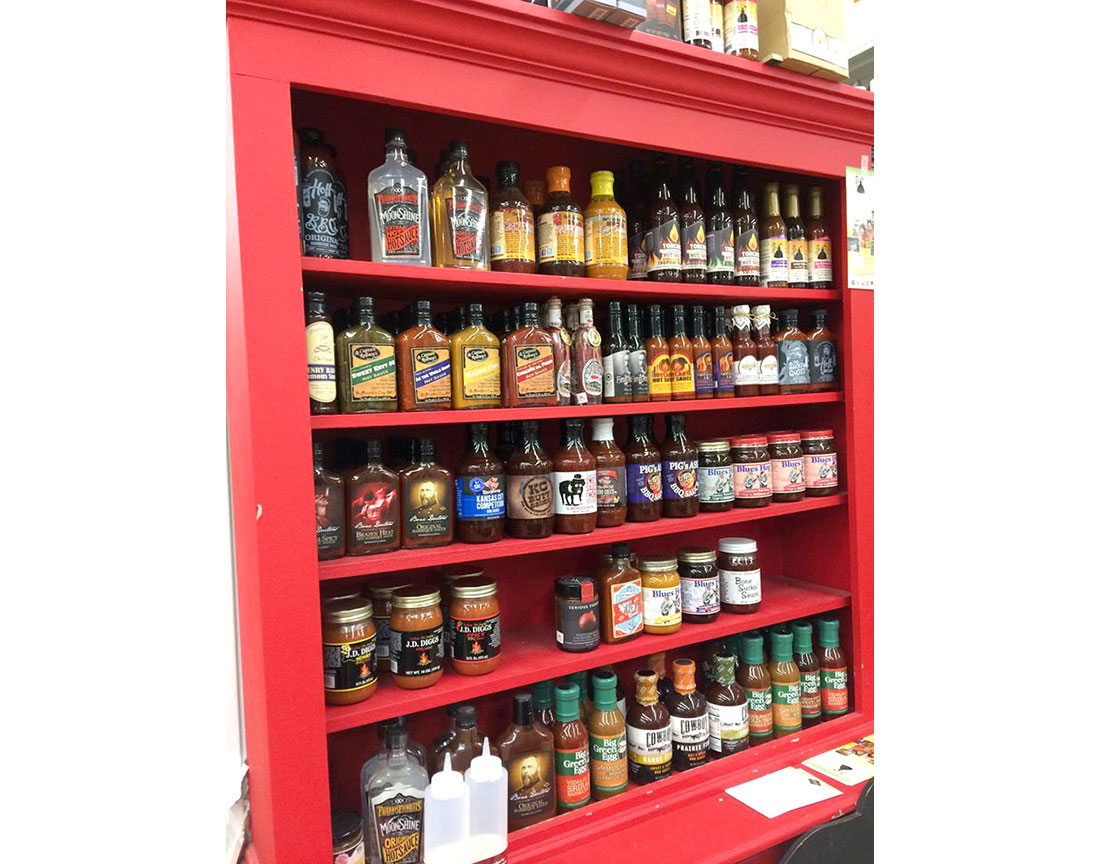 A whole cabinet is devoted to a wide variety of barbecue sauces.