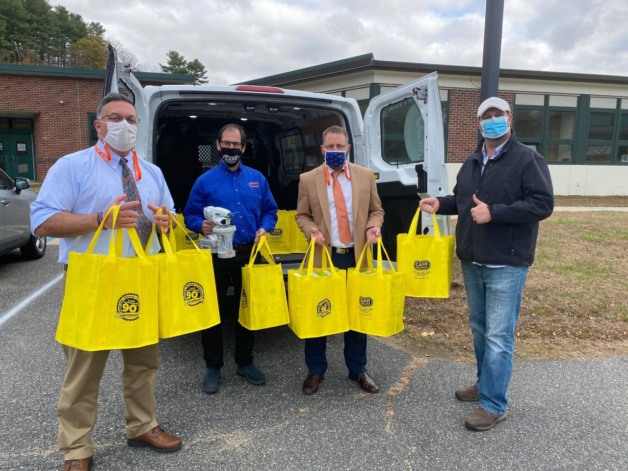 Bart Raser (second from left) of Carr Hardware donates PPE to Lee Public Schools.