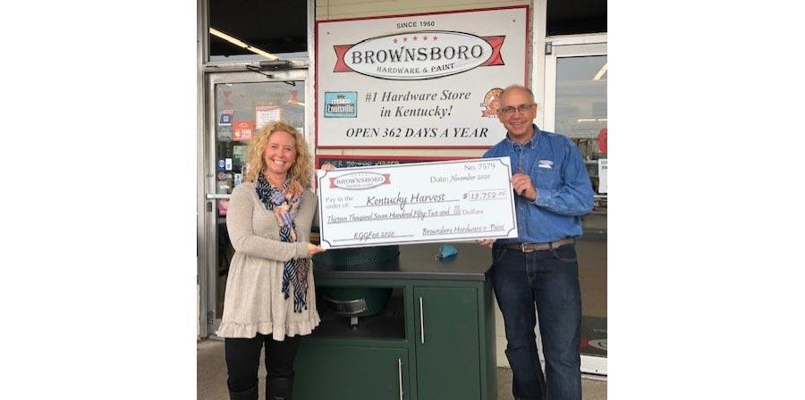 Jim Lehrer presents a check to Heather Stewart of Kentucky Harvest