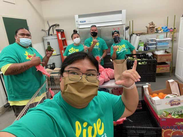 HPM Building Supply owner-employees pack meals at the Hawaii Food Basket as part of the 100 Acts of Service initiative to commemorate the company's centennial anniversary this year.
